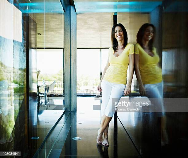 Woman standing barefoot in hallway of home smiling