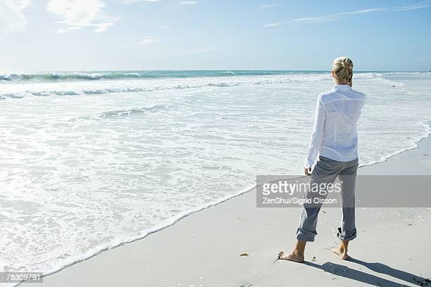 Woman standing barefoot on beach, using cell phone, rear view