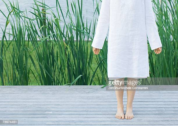 Woman standing barefoot on deck