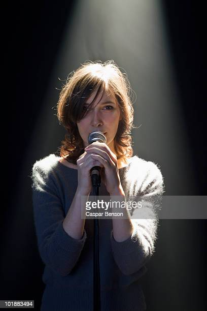 A Woman Standing Behind A Microphone
