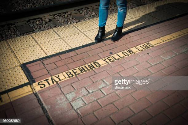 woman standing behind a yellow line on a train platform - rébellion photos et images de collection