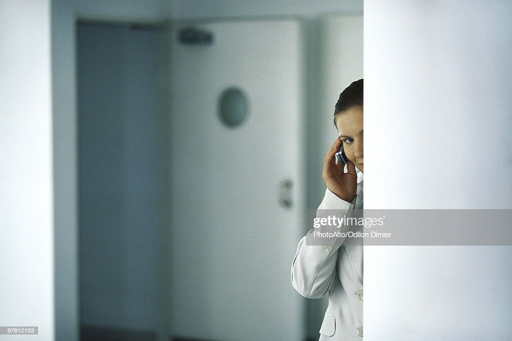Woman standing behind column discretely speaking on cell phone : Stock Photo
