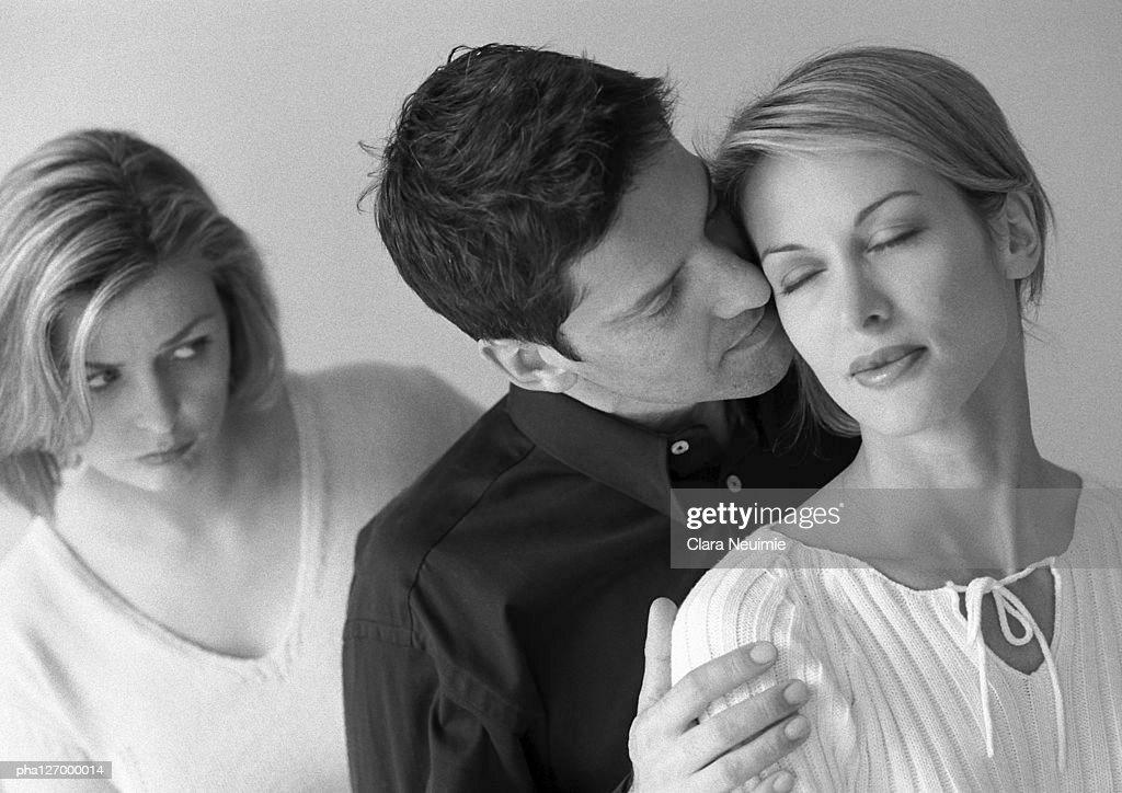 Woman standing behind couple hugging, b&w : Stockfoto