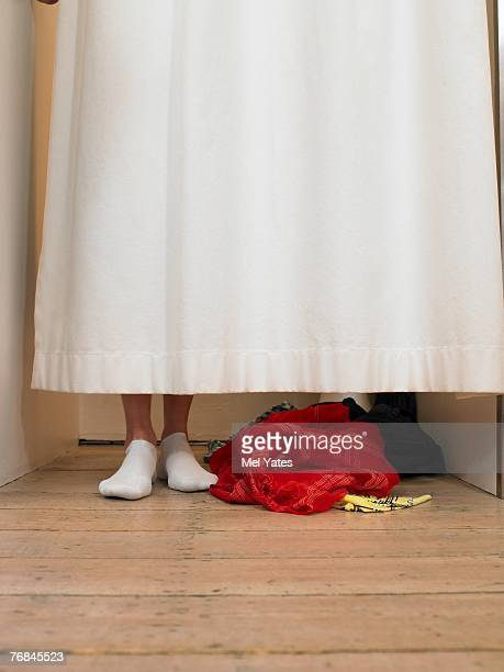 Woman standing behind curtain in changing room, low section
