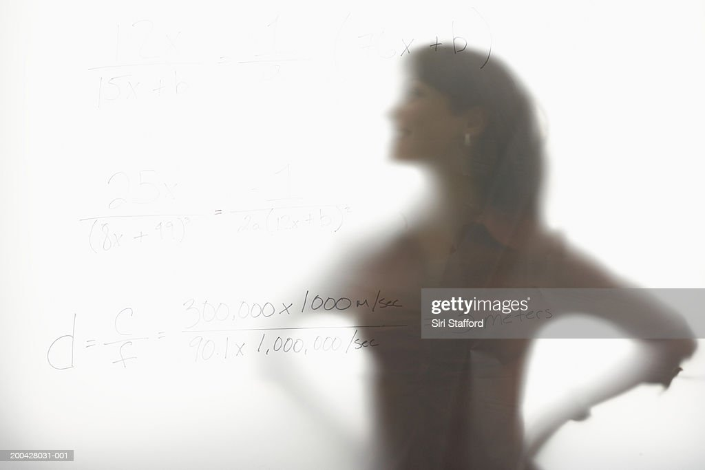 Woman standing behind frosted glass : Stock Photo