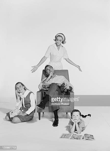 Woman standing behind man sitting on chair, children playing around