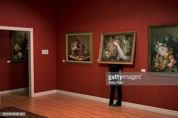 woman standing behind painting on wall in art gallery - hiding stock pictures, royalty-free photos & images