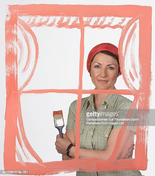 """woman standing behind transparent painting of window on glass, studio shot, portrait - """"compassionate eye"""" stockfoto's en -beelden"""
