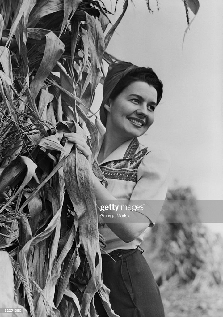Woman standing behind tree, smiling : Stock Photo