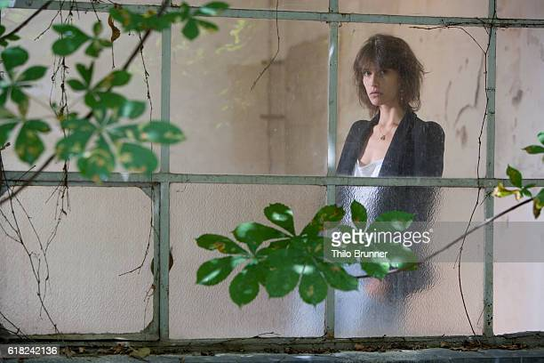 Woman standing behind window