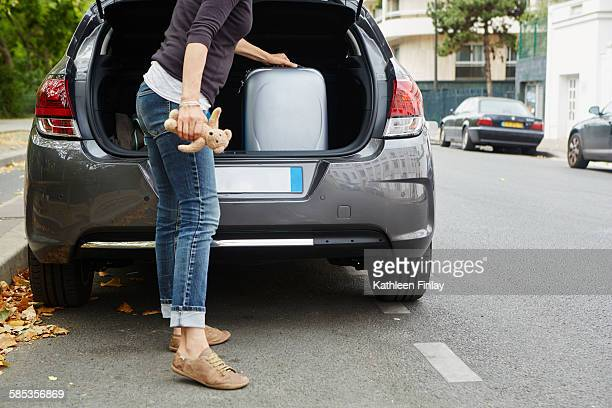 woman standing beside car, putting suitcase in open boot - next to stock pictures, royalty-free photos & images