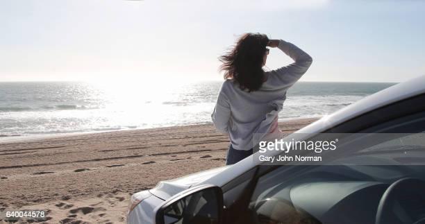 Woman standing beside her car looking towards ocean.