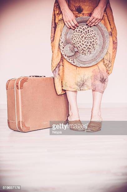 Woman standing beside suitcase