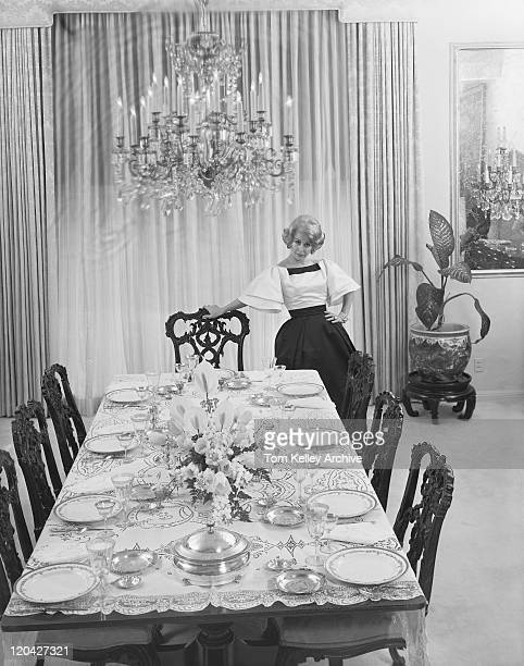 Woman standing beside table setting, portrait