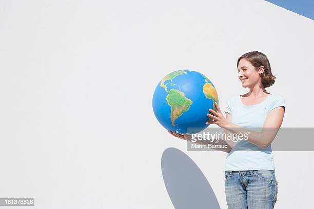 Woman standing beside wall with globe