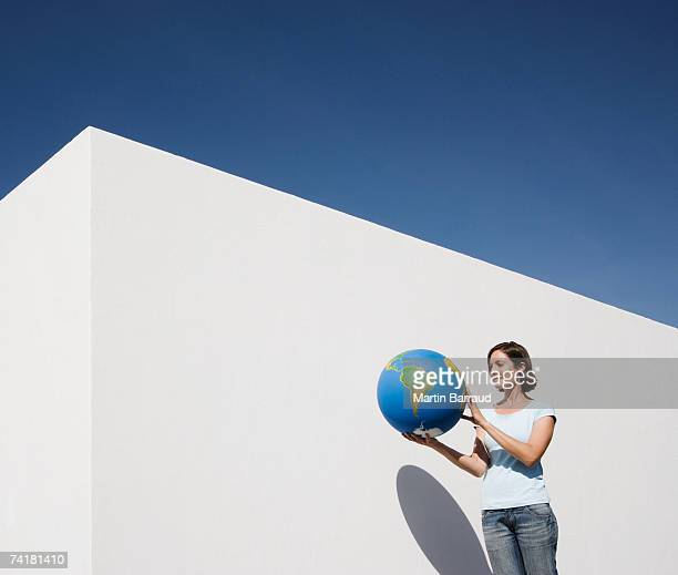 woman standing beside wall with globe - world kindness day stock photos and pictures