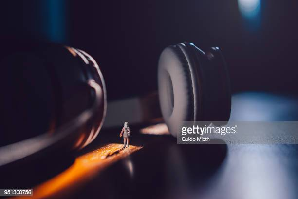 woman standing between big earphones - big brother orwellian concept stock pictures, royalty-free photos & images