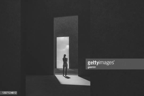 woman standing between passages - light at the end of the tunnel stock pictures, royalty-free photos & images