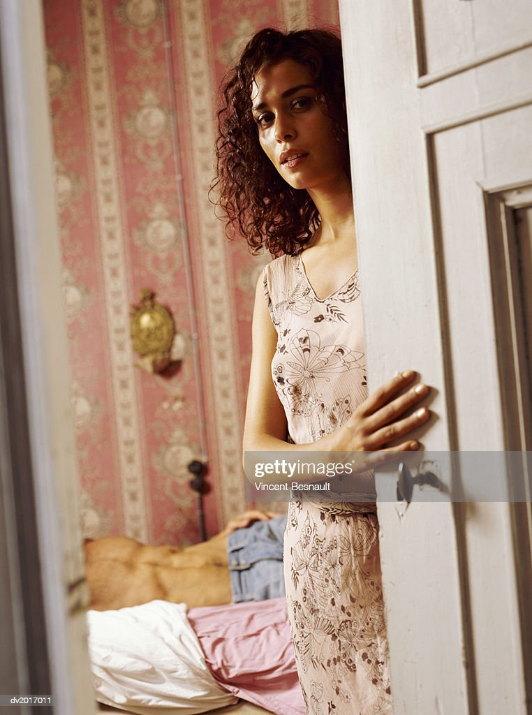 Woman Standing By a Bedroom Door, Man Lying on Bed in Background : Stock Photo