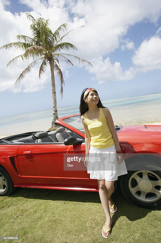 Woman Standing by a Convertible by the Beach : Stock Photo