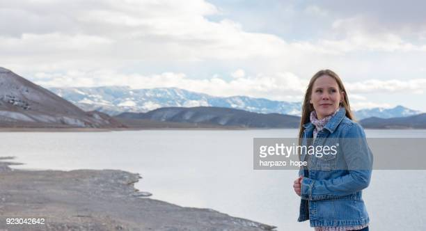 Woman standing by a lake in winter.