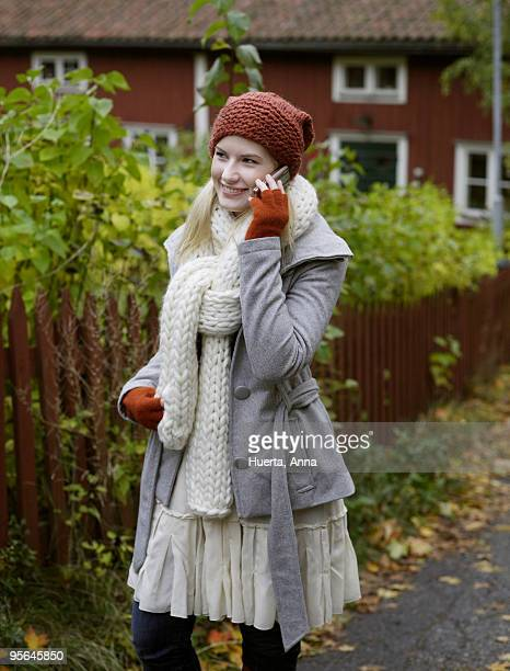 a woman standing by a red fence in the autumn, sweden. - anna cabana photos et images de collection