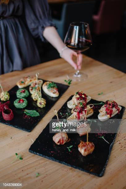 woman standing by a table with appetizers holding a glass of red wine - tapas stock photos and pictures
