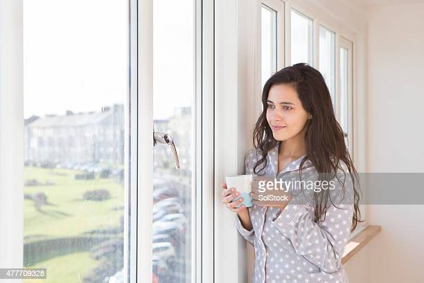 Woman Standing by a Window Drinking Coffee in her Pyjamas