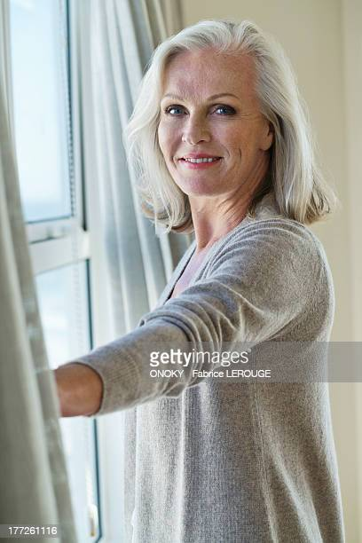 woman standing by a window - 65 69 ans photos et images de collection