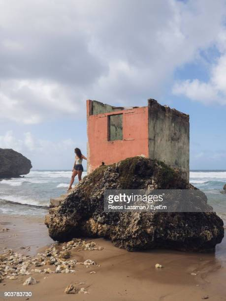 Woman Standing By Abandoned Built Structure At Beach