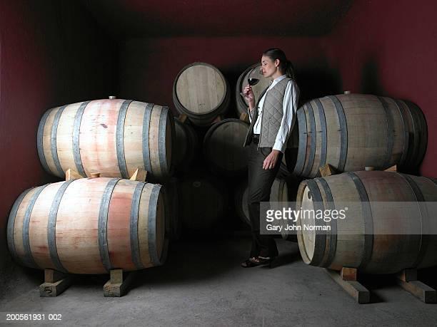 Woman standing by barrels in wine cellar