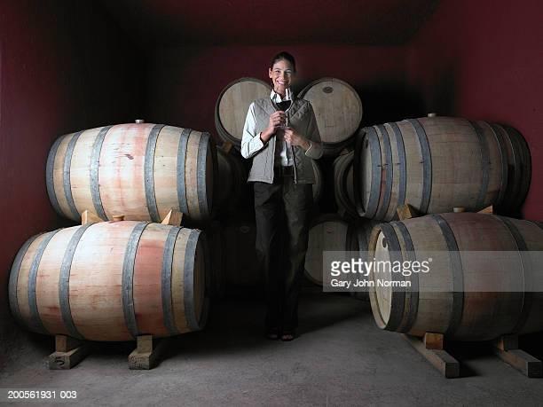 Woman standing by barrels in wine cellar, smiling, portrait