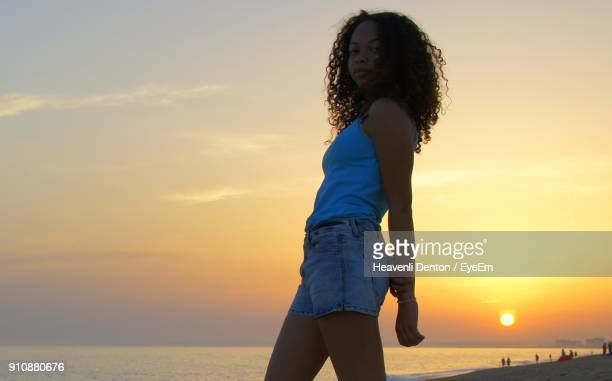 Woman Standing By Beach Against Sky During Sunset