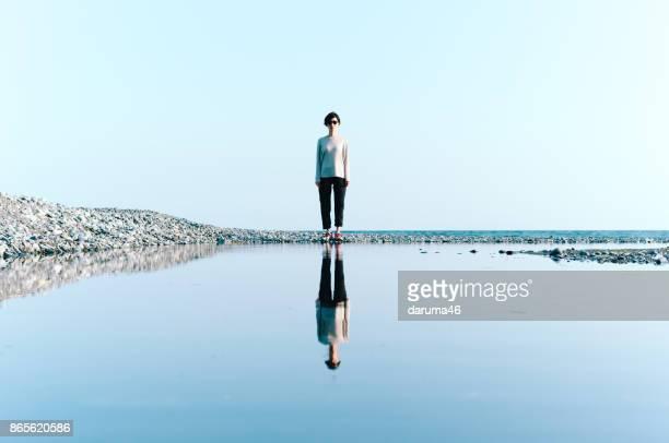 ビーチの大きな水たまりに反映して立っている女性