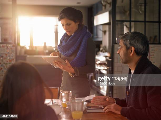 woman standing by breakfast table looking at iPad