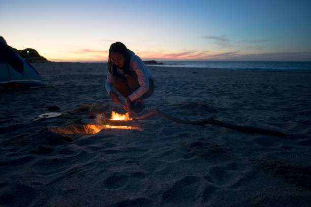 Woman Standing By Campfire On Beach Against Sky During Sunset