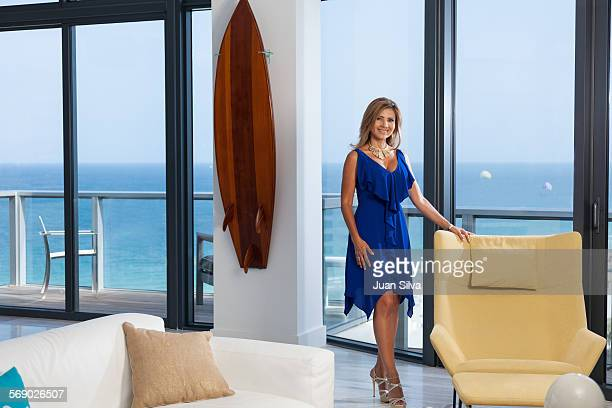 Woman standing by chair at apartment with a view