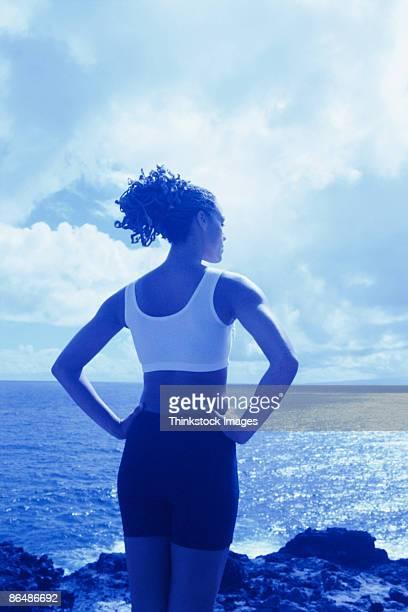 woman standing by coast - thinkstock stock-fotos und bilder