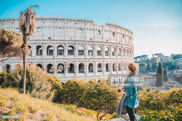 woman standing by coliseum against sky - colosseum stock pictures, royalty-free photos & images