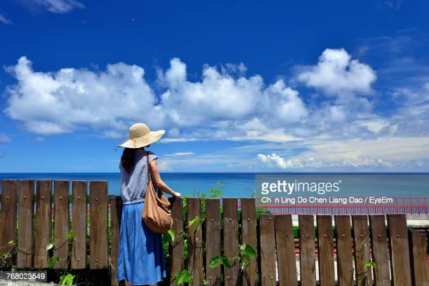 Woman Standing By Fence At Beach Against Sky