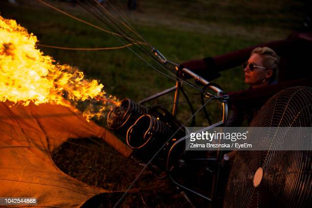Woman Standing By Fire At Night