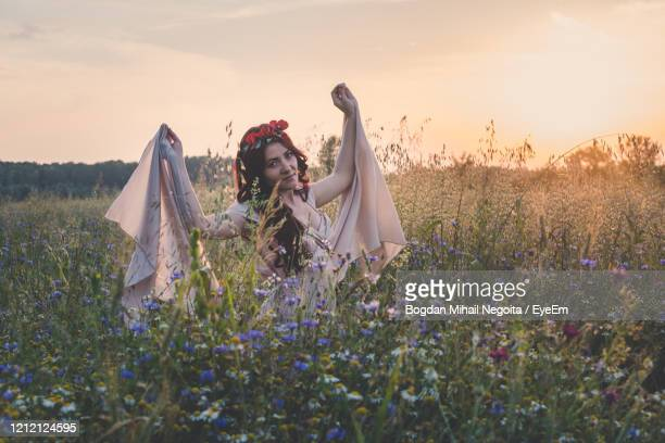 woman standing by flowering plants on field against sky - bogdan negoita stock pictures, royalty-free photos & images