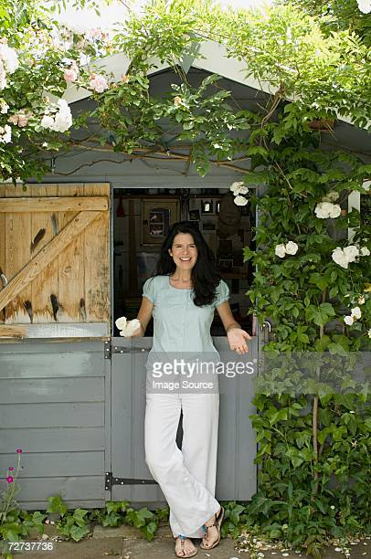 Woman standing by garden shed
