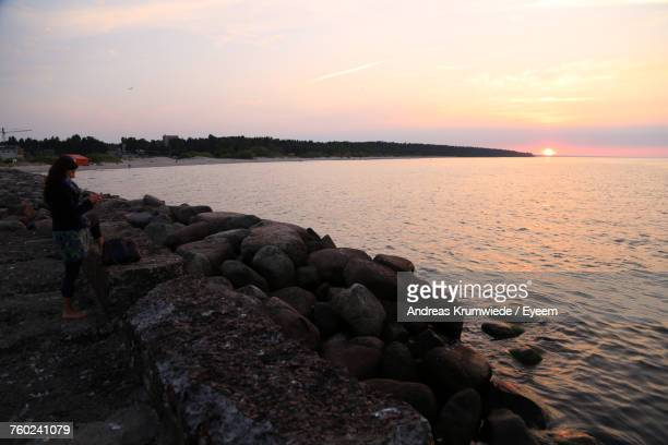 Woman Standing By Groyne At Beach Against Sky During Sunset