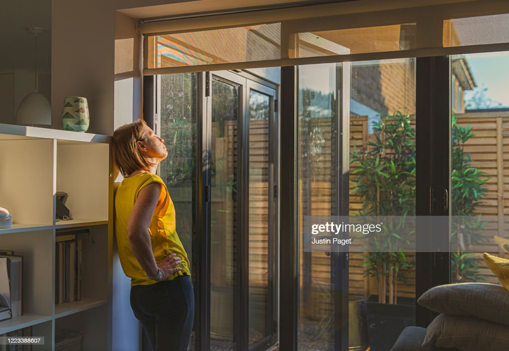 Woman standing by her back door : Stockfoto