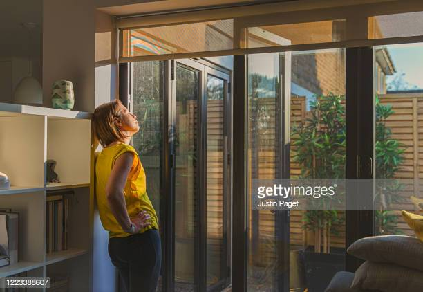 woman standing by her back door - boredom stock pictures, royalty-free photos & images