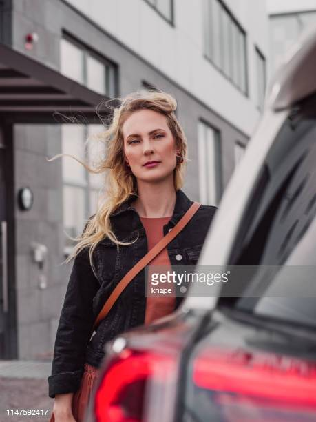 woman standing by her car outdoors - next to stock pictures, royalty-free photos & images
