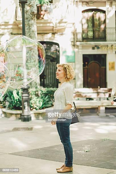woman standing by huge bubbles on footpath in city - bortes fotografías e imágenes de stock