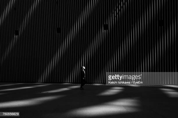woman standing by illuminated wall - black and white ストックフォトと画像