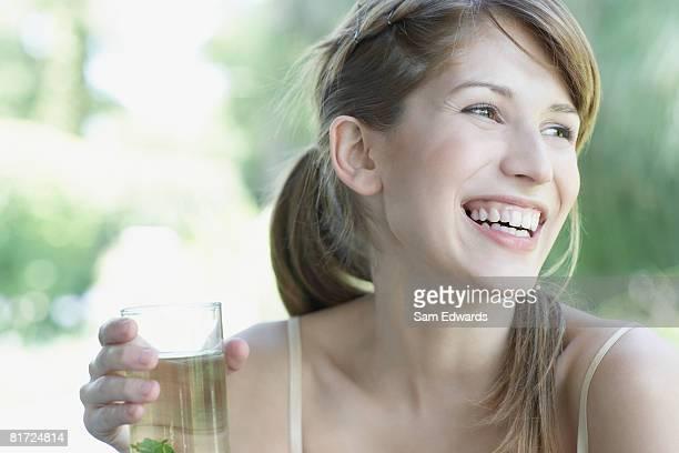 Frau stehend durch große Fenster holding Kräuter Getränke und Lachen